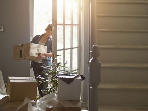 A woman carries a box into new home through front door
