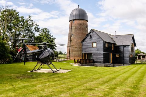Brick tower mill attached to black house with green gardens and helicopter