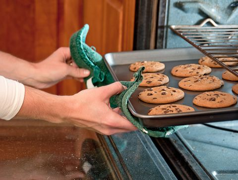 Pair of hands pulling a tray of baked cookies out of the oven