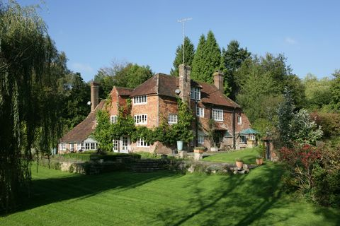 Exterior shot of the country house where Winnie the Pooh author lived surrounded by grass and trees