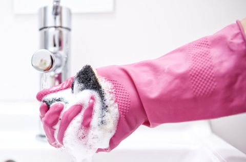 Woman cleaning bathroom sink with sponge