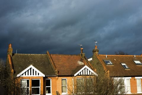 Threatening clouds over sun lit houses