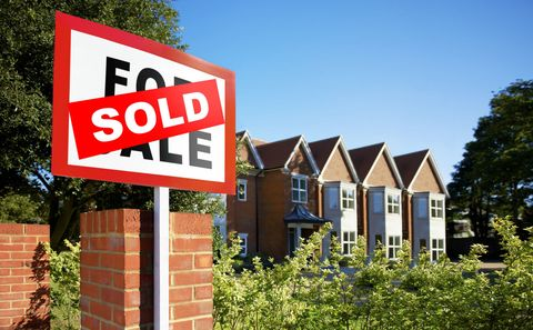 Sold sign outside row of properties on a sunny day