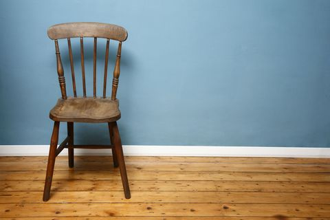 Bare wood flooring with wooden chair and blue walls