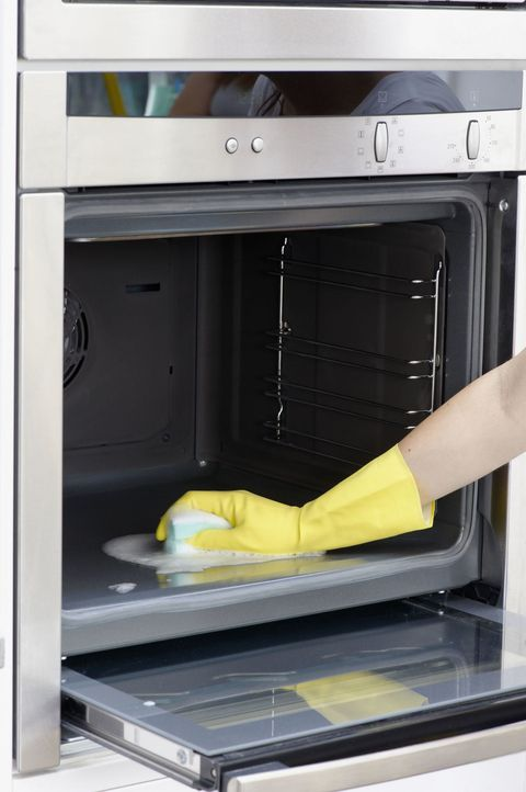 Woman Wearing Yellow Washing Up Glove To Clean Inside Oven Using Sponge