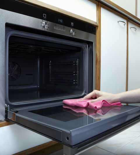 Women Cleaning The Oven With Towel