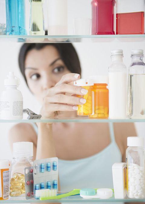 Woman looking at medicine cabinet