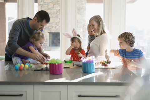 Family colouring Easter eggs in kitchen