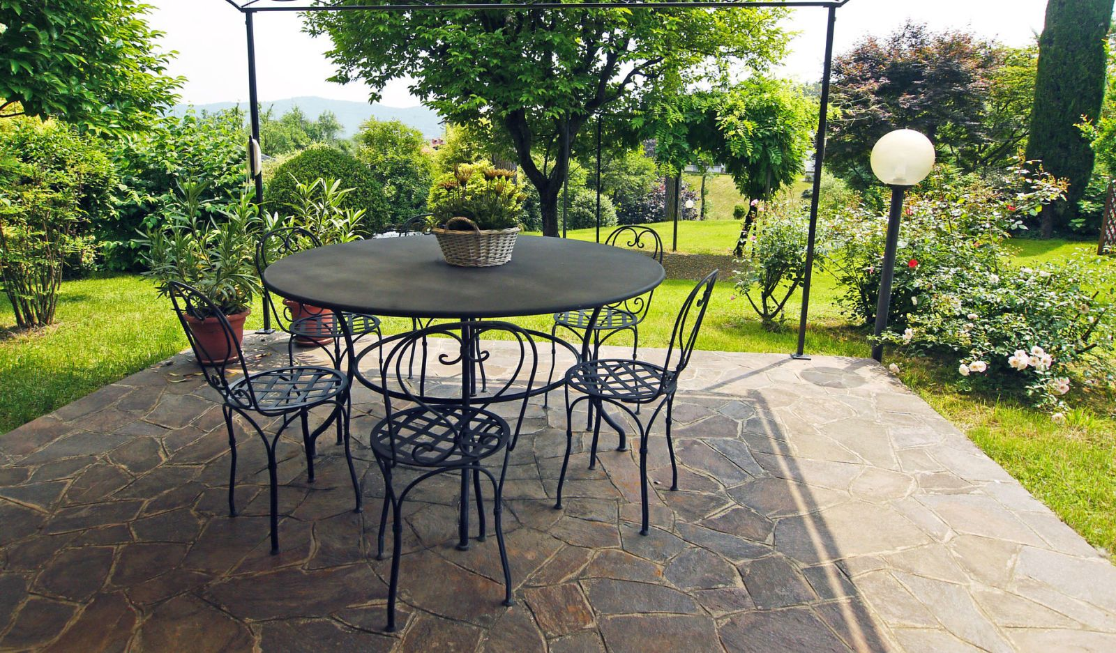 Covered Patio With View On Garden: Cosy Garden Corner With Round Wrought  Iron Table And