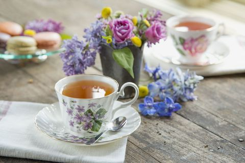 Spring bouquet among teacups and macarons on table