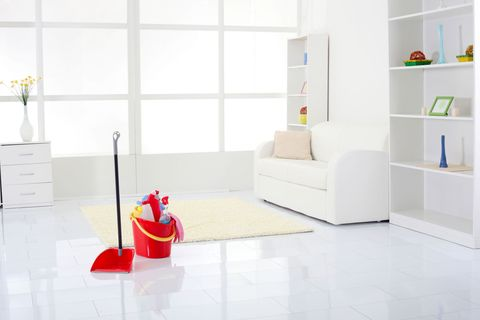 Spotlessly clean white living room - cleaning products in bucket on floor