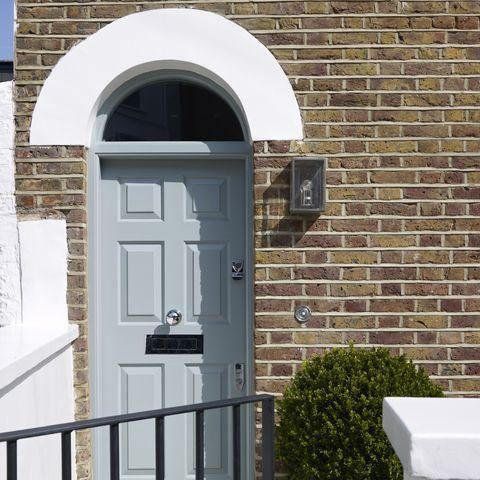 pale blue front door in brick house