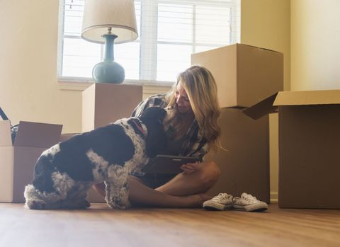 Young woman with dog in their new house