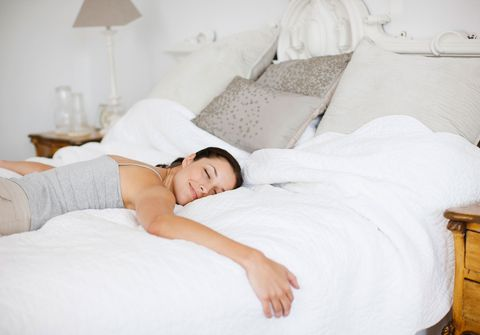 Woman looks happy and peaceful as she sleeps in bed