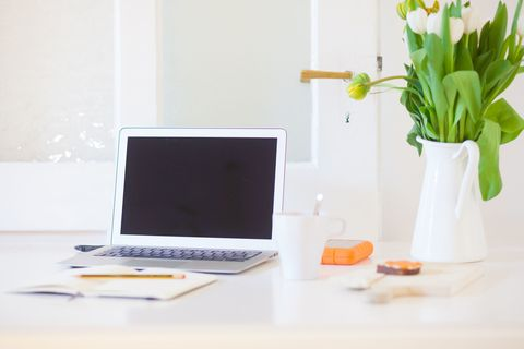 Working from home. Laptop on a desk in a living room or modern kitchen.