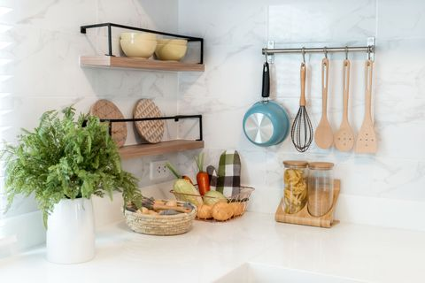 Kitchen wood utensils, chef accessories. Hanging copper kitchen with white tiles wall