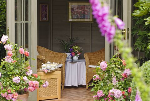 Summerhouse with wicker furniture and afternoon tea set, June