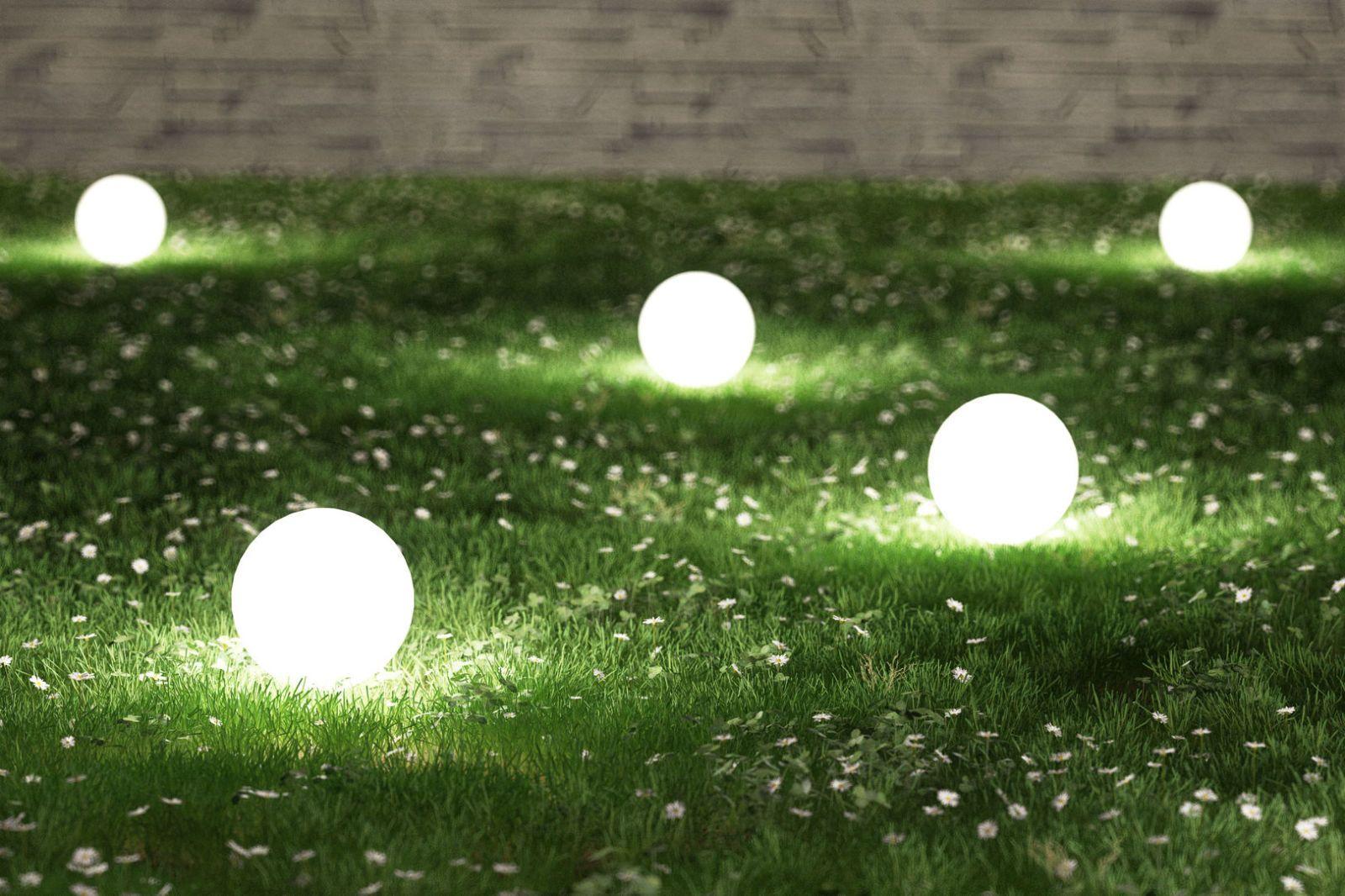 Illuminated Lamps On Grassy Field In Garden