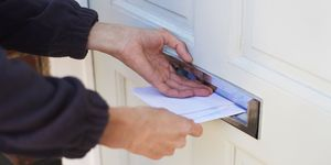 Close up of postman delivering post through resident's letterbox