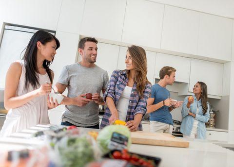 Flatmates standing in kitchen