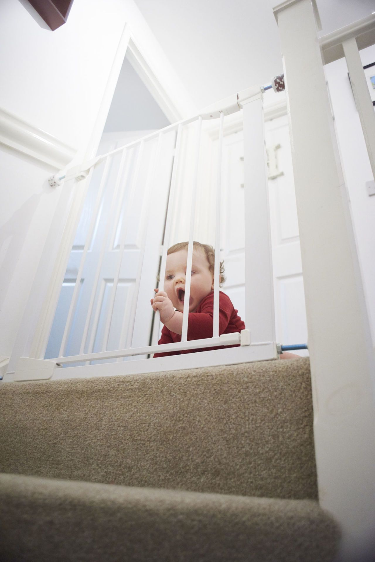 Baby Safety Gate On Stairs: Baby Boy On The Landing Of His Home. He