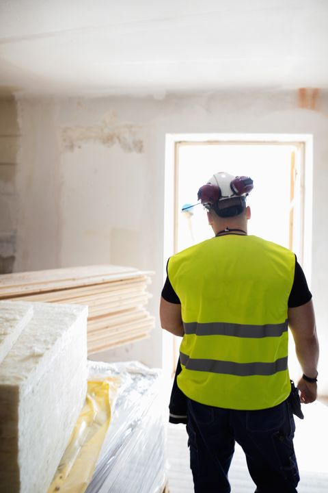 Rear view of man standing in brightly lit room at construction site