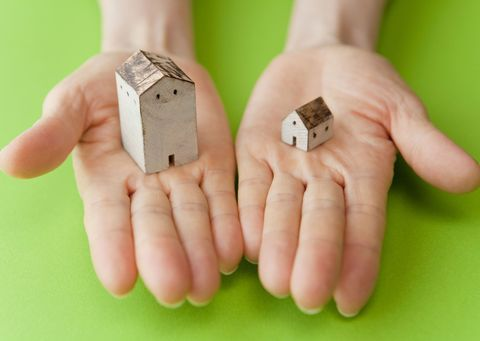 Close up of hands holding miniature houses