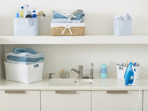 Items used for washing and cleaning, and stack of folded towels, next to and on shelf above sink in domestic laundry room