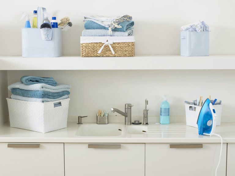 Items Used For Washing And Cleaning And Stack Of Folded Towels Next To And
