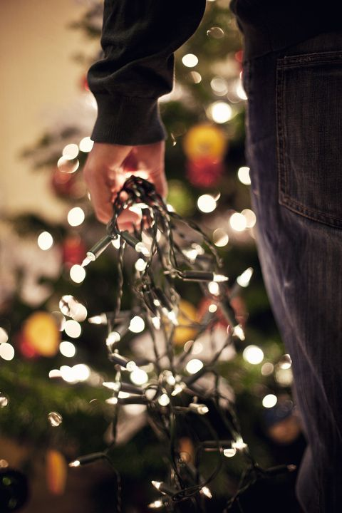 man putting up christmas decorations holding fairy lights
