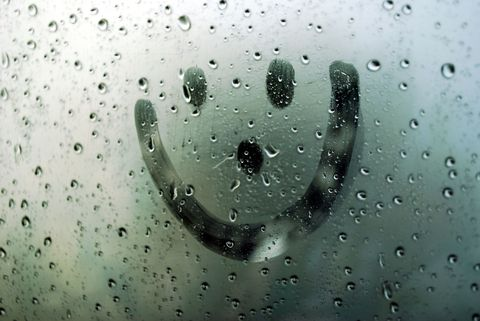 Smiley face on wet window from rain