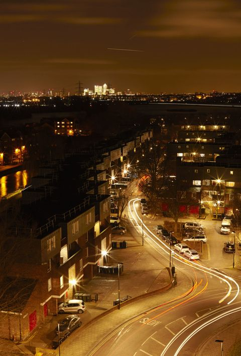 Low rise London housing in Tottenham Hale with Canary Wharf city skyline in the background. Light trails from cars.