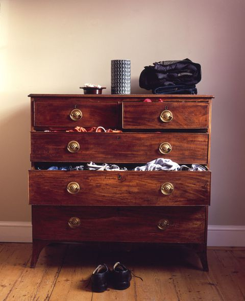 Shoes on floor by chest of drawers with drawers pulled open