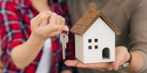 Couple with keys and wooden house modelling