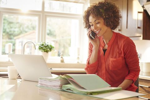 Woman sits in her kitchen and works through some paperwork whilst chatting on the phone