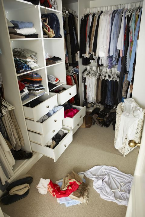 Messy wardrobe with clothes on floor