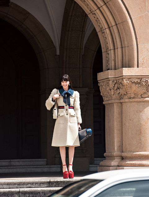 Clothing, Coat, Outerwear, Standing, Arch, Street fashion, Bag, Boot, Arcade, Column,
