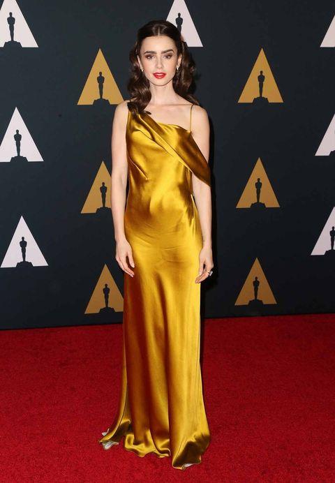 Fashion model, Red carpet, Carpet, Clothing, Dress, Yellow, Gown, Shoulder, Flooring, Fashion,