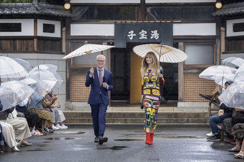 Umbrella, Yellow, Snapshot, Street, Fashion accessory, Rain, Pedestrian, Architecture, Temple, Street fashion,