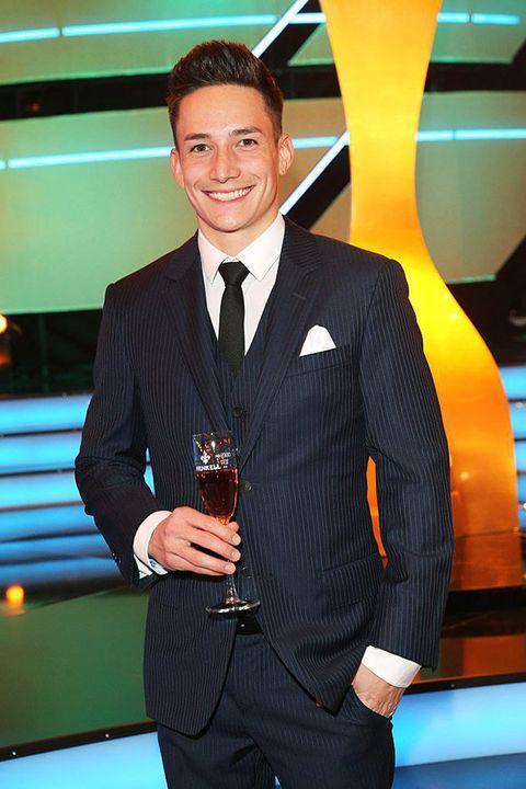 Suit, Formal wear, Tuxedo, Games, White-collar worker, Award, Recreation, Television presenter, Blazer,