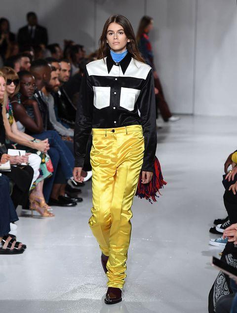 Fashion model, Fashion show, Runway, Fashion, Clothing, Fashion design, Yellow, Event, Footwear, Waist,
