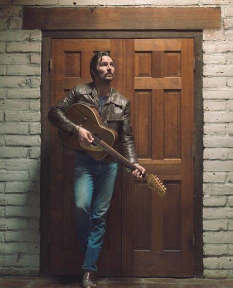 Wood, Musical instrument, Musician, Jeans, Guitar, Wall, Brick, Door, Guitarist, Plucked string instruments,