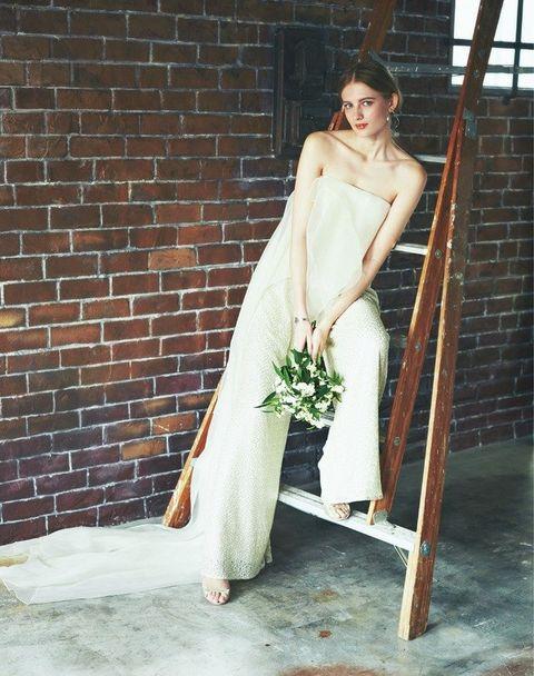 Hat, Dress, Brick, Waist, Stairs, Bridal clothing, Wedding dress, Gown, Brickwork, Bride,