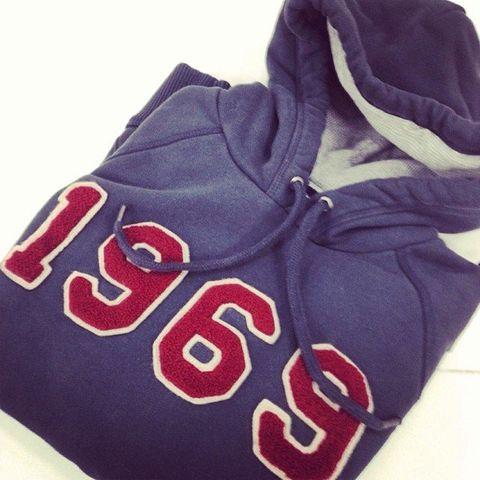Textile, White, Font, Carmine, Sports jersey, Symbol, Hood, Stole,