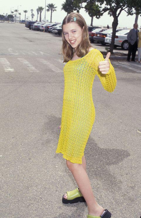 Yellow, Dress, Human leg, Asphalt, Road surface, Street fashion, Slipper, Street, One-piece garment, Day dress,