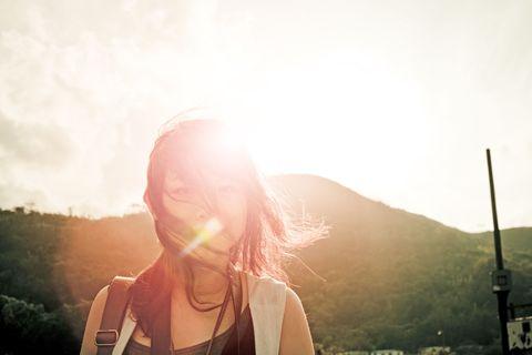 Mammal, Sun, Sunlight, Summer, Lens flare, Cap, People in nature, Light, Backlighting, Long hair,