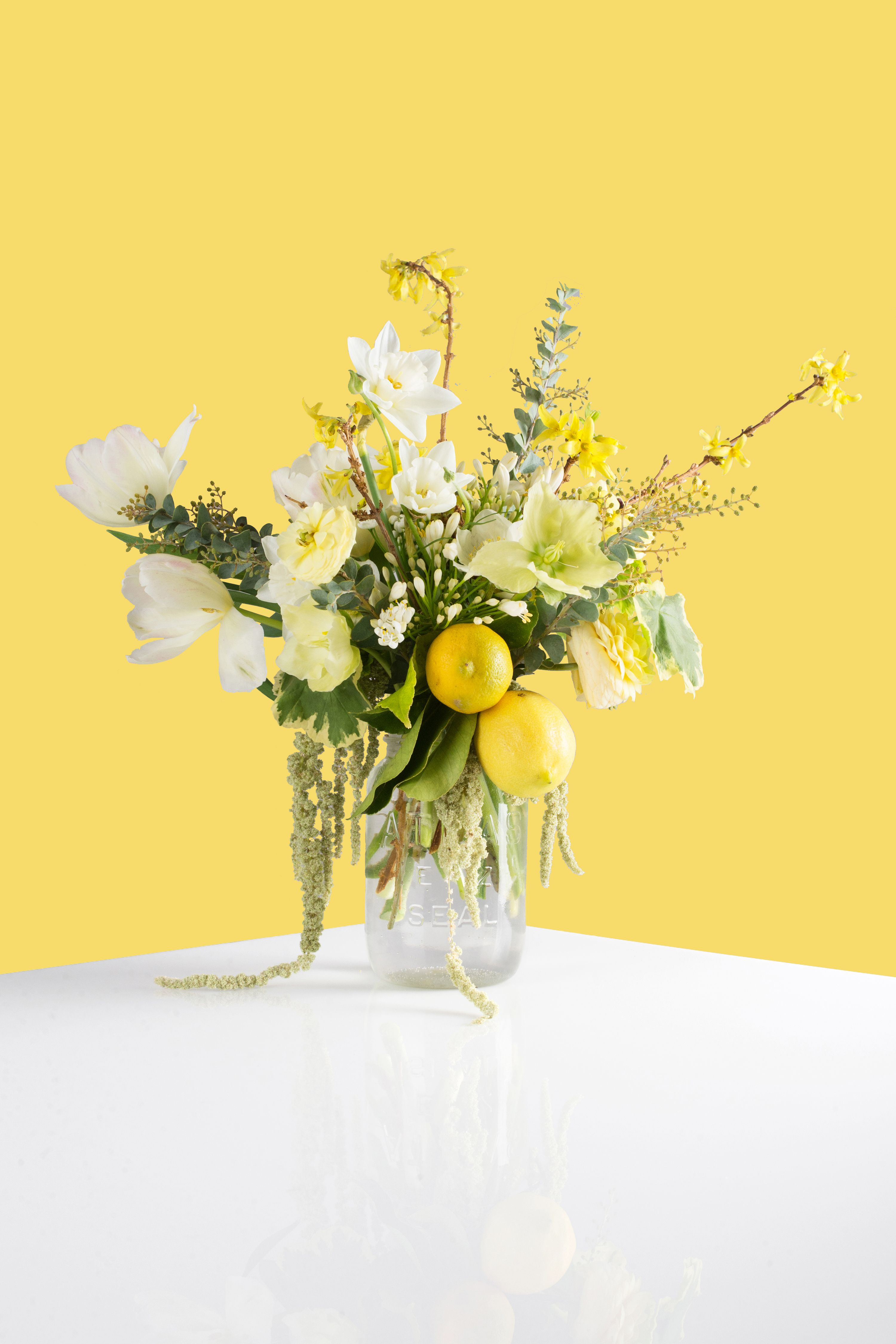 <p>Refreshingly unpretentious, this arrangement iscomposed of earth's greatest healing agents:lemons, allium (onion), and geranium, allin avintage ball jar that looks like it's been nabbed from your grandmother's kitchen.</p> <p><em>Materials: Tulips, Daffodils, Ranunculus, Acacia, Hellbores (Winter Rose), Forsythia, Agapanthus, Allium,Geranium, Amaranth</em></p> <p><em>Retails at $150.</em></p>