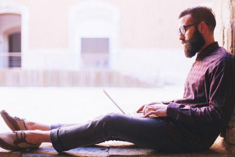 Human body, Facial hair, Sitting, Beard, Street fashion, Knee, Moustache, Reading, Lap, Boot,