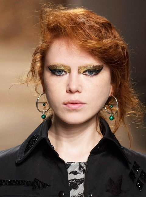 <p>NARS' Aaron de Mey served up maaajor glam rock realness to match a modern, wet-finish take on '80s tidal wave hair. He not only went with a super-pronounced, Cleopatra-worthy cat eye, but topped it off by layering gold sparkles on <i>thick</i>. You could literally wear this look with anything—an LBD or a T-shirt and jeans—and it's instantly Halloween-worthy.</p>