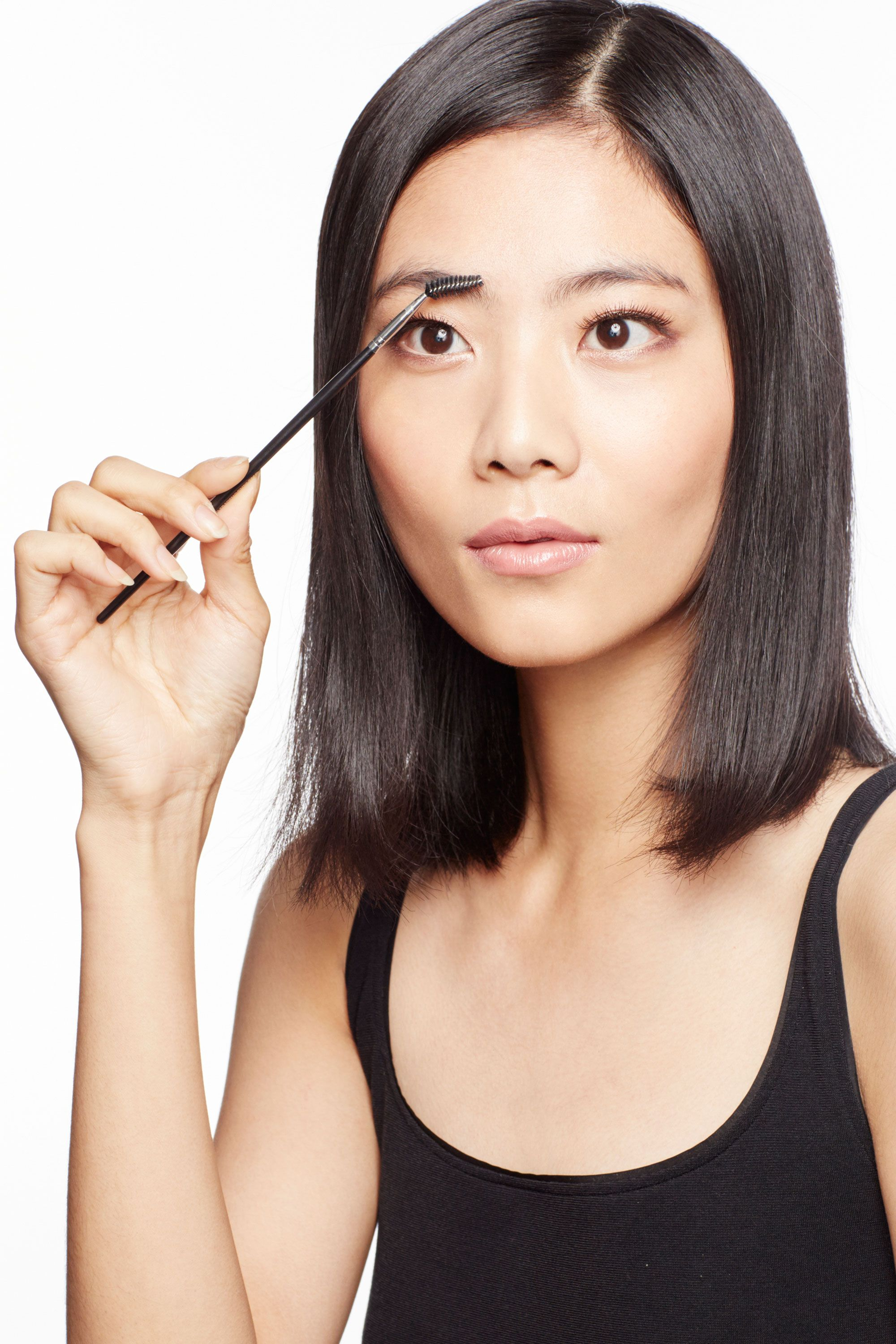 "<p>Using a spoolie, brush brows against the grain. ""This help expose your skin, so the crayon has something to adhere to,"" says makeup artist Nigel Stanislaus.</p>"